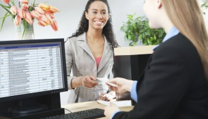 Bank Teller Servicing Banking Customer Transaction Over Retail Counter