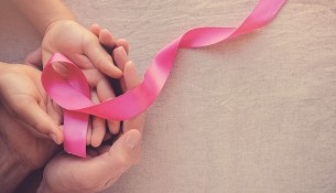 Adult and child hands holding pink ribbons, Breast cancer awareness, abdominal cancer awareness and October Pink panoramic background