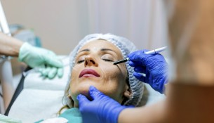 Beautician touch and draw correction lines on woman face