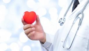 medico-segurando-uma-bola-de-coracao-vermelho-no-fundo-hospitalar_7636-924