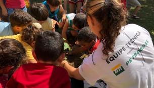Crianças plantando em ação do Projeto Semeando Água