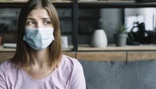mulher-doente-usando-mascara-protetora-em-casa_23-2147953259