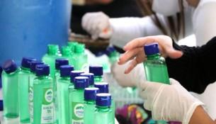servidoras envasam alcool gel